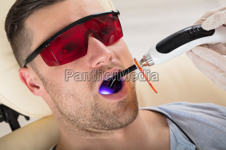 mans teeth are treated by lit