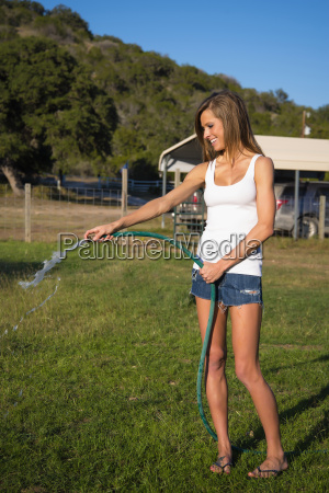 usa texas young woman watering lawn