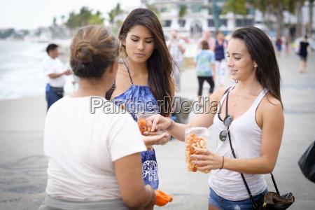mexico puerto vallarta women buying chicharrones