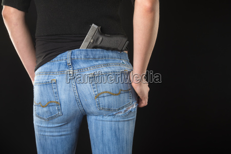 young woman with handgun standing against