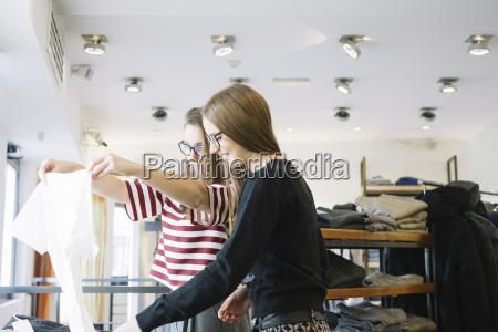 zwei junge frauen in einem modegeschaeft