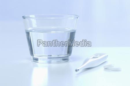 klinisches thermometre mit glas wasser und