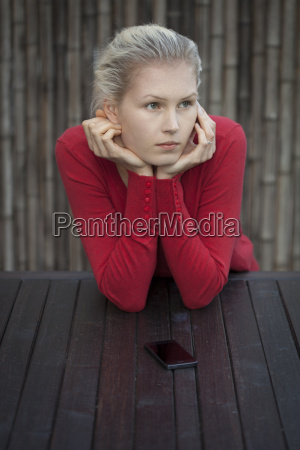 young woman with smart phone waiting