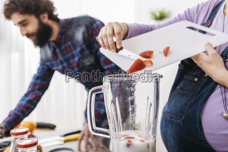pregnant woman preparing smoothie with fresh