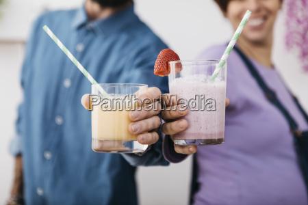 paare mit glaesern verschiedener smoothies bereit
