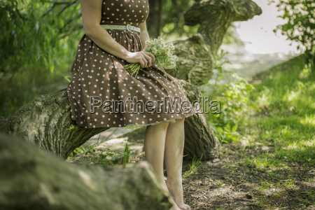 woman sitting on tree trunk holding