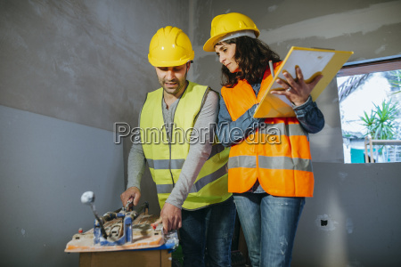 woman supervising worker cutting tile