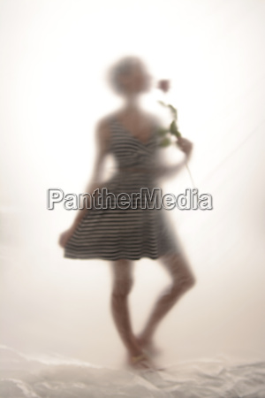 young woman with rose behind foil