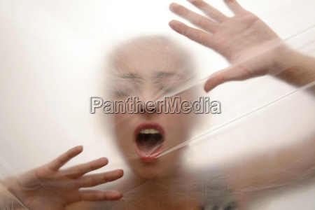 young woman screaming behind foil