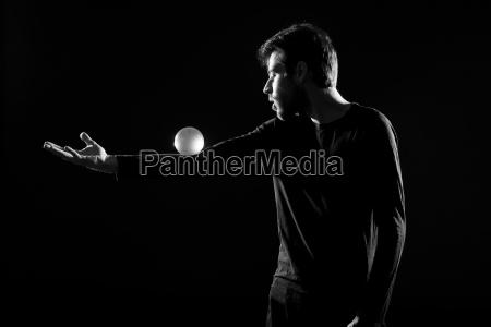 mann jongliert mit kristallkugel vor schwarzem