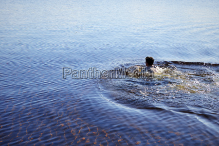 sweden leksand man swimming in lake