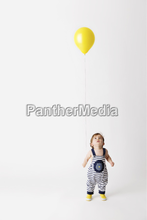 toddler standing in front of white
