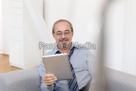 germany senior man sitting on sofa