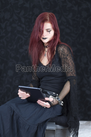 young woman wearing gothic fashion holding