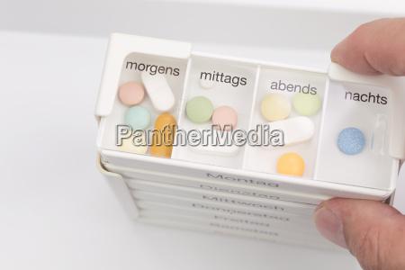 menschliche hand haelt verschiedene pille box