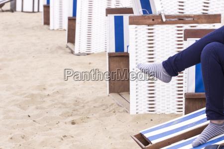 junge frau sitzt in kapuzen strand