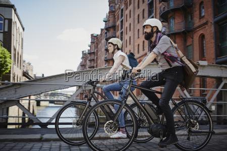 germany hamburg couple riding electric bicycles