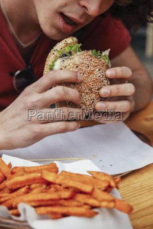young man eating vegan hamburger and
