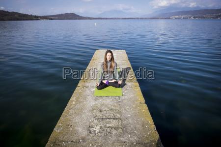 uebendes yoga der frau auf einem