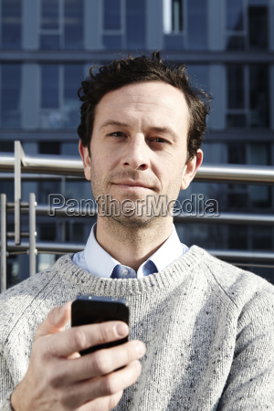 serious looking man with smartphone