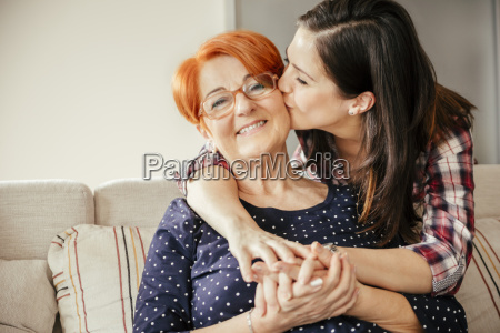 happy adult daughter embracing and kissing