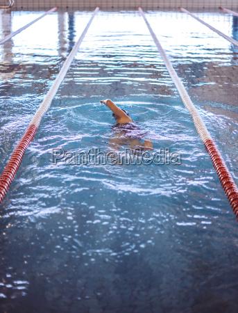 weiblicher schwimmer im innenpool