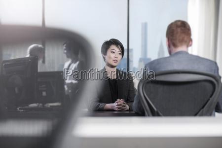 woman and man talking at desk