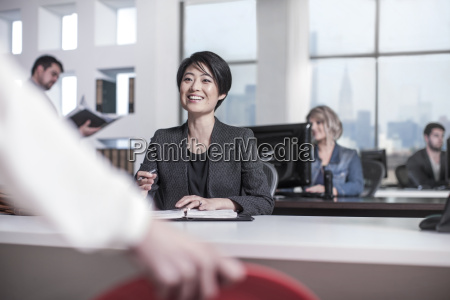 smiling woman sitting at desk in