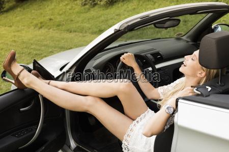 lachende junge frau die im cabriolet