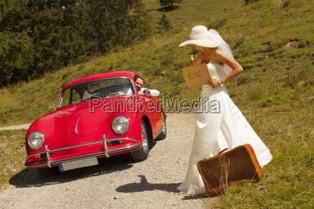 bride with suitcase waiting wayside of