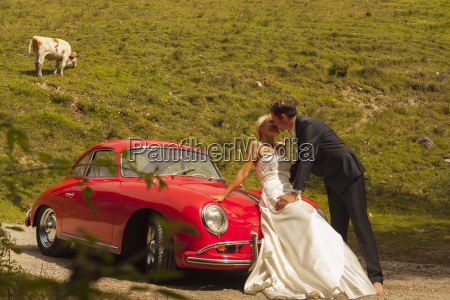 groom kissing bride leaning on car