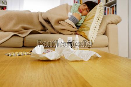 kranke frau die auf sofa liegt