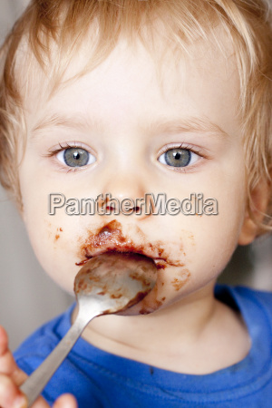 girl nibbling chocolate with spoon close