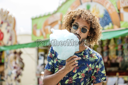 young man eating candy floss at