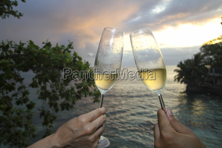 two people holding champagne flutes at