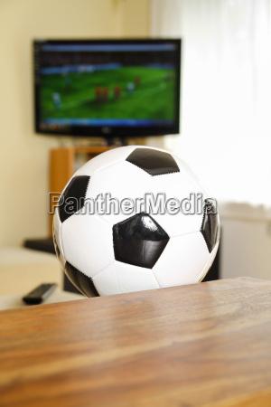 wohnzimmer mit tv und fussball