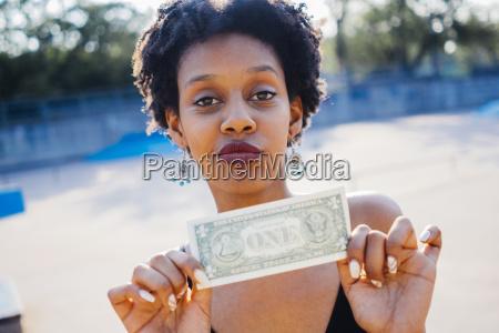 kvindeportraet der viser en dollarseddel naerbillede