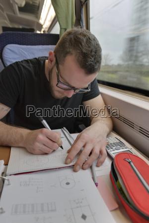junger mann arbeitet an matheproblemen im