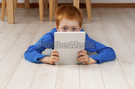 little boy with tablet computer lying