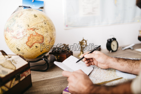 young man planning journey taking notes