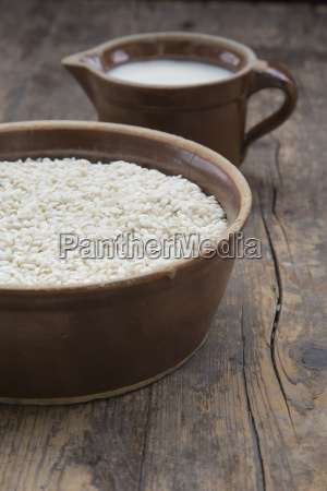 ingredients of rice pudding on wooden