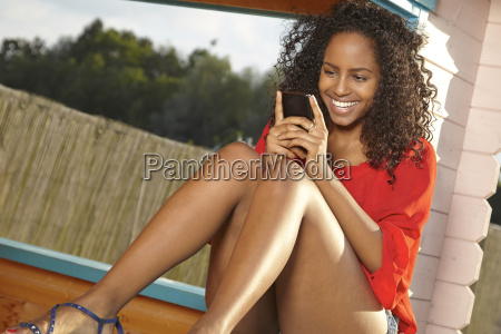 smiling young woman reading sms