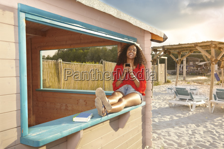 laughing young woman with smartphone at