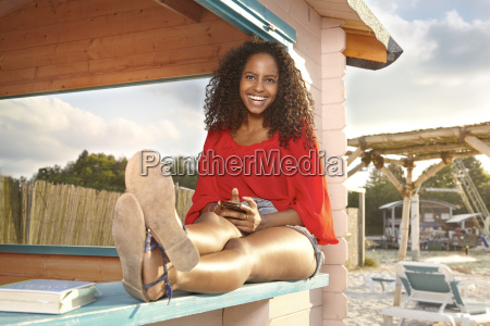 smiling young woman with smartphone at