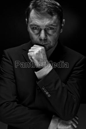 portrait of mature man against black