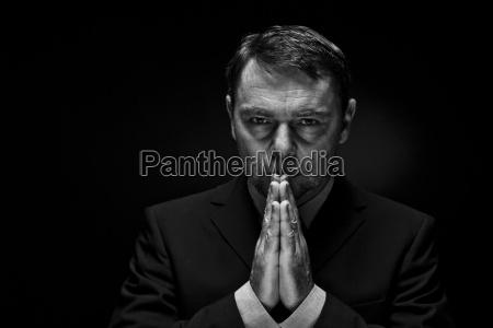 mature man in full suit praying