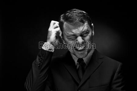 mature man clenching teeth against black