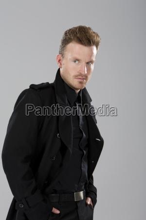 mittelerwachsener mann in schwarzem mantel vor