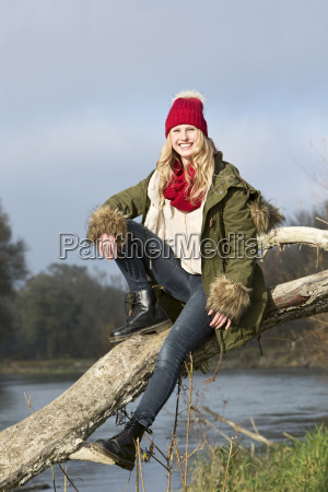 smiling young woman sitting at tree
