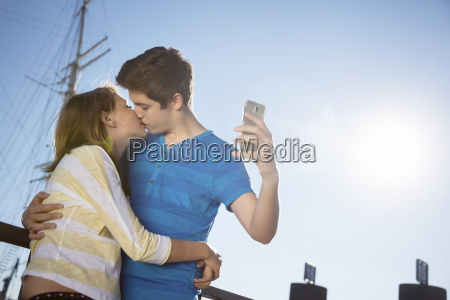 teenage couple kissing while photographing themself